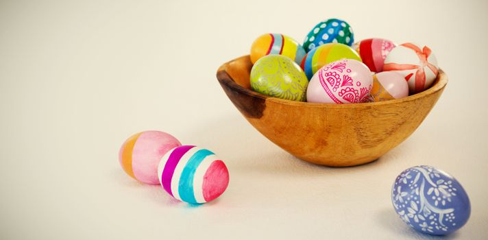 Colorful Easter eggs in wooden bowl on white background