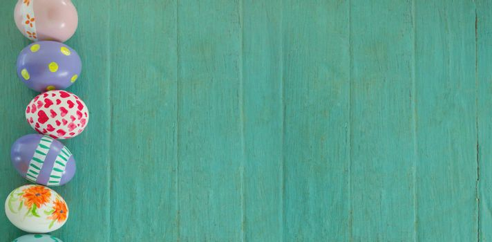 Overhead view of painted Easter eggs on turquoise wooden background