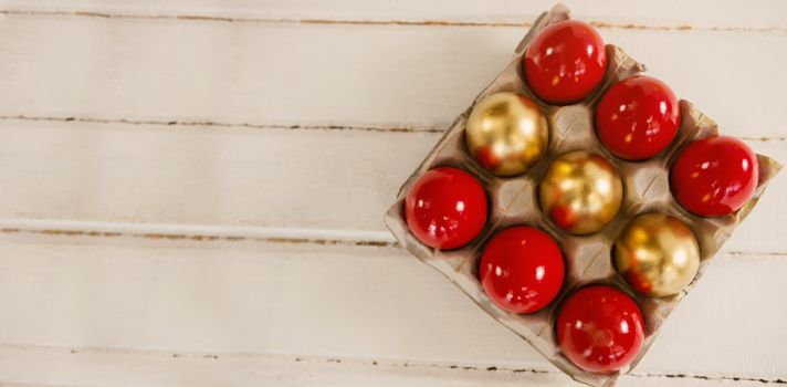 Red and golden Easter eggs in carton on wooden background