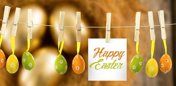 Happy easter logo against golden easter eggs in the nest