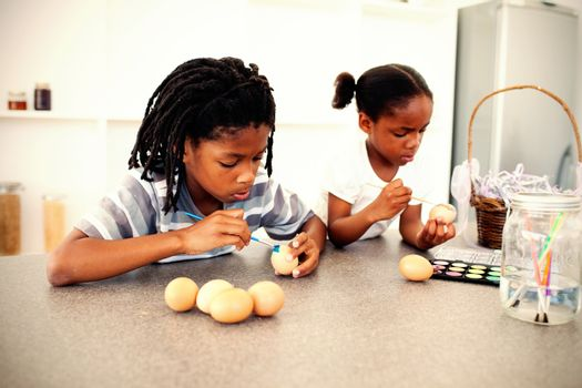 Concentrated siblings painting eggs