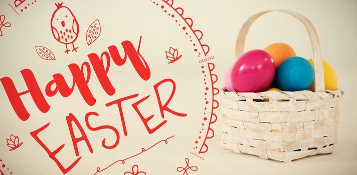 Happy easter logo against various easter eggs in wicker basket