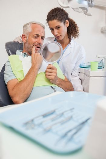 Patient showing dentist the problem in the mirror at the dental clinic