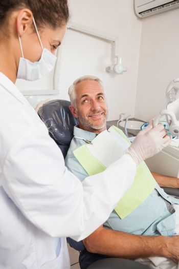 Patient smiling at dentist in the chair at the dental clinic