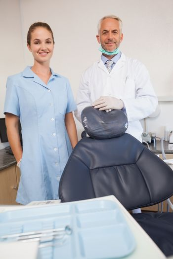 Dentist and assistant smiling at camera at the dental clinic