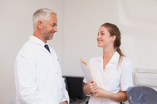 Dentist and dental assistant smiling at each other at the dental clinic