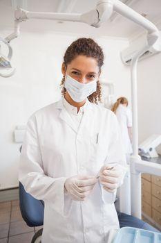 Dentist examining her tools on a tray looking at camera at the dental clinic