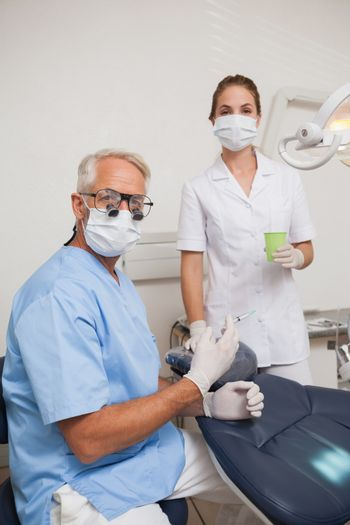 Dentist and assistant looking at camera by the chair at the dental clinic