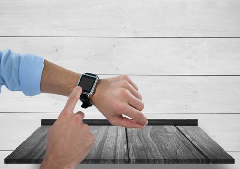 Arms with smart watch against wood