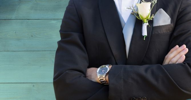 Groom mid section against teal wood panel