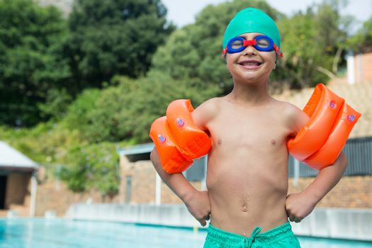 Boy wearing arm bands standing at poolside