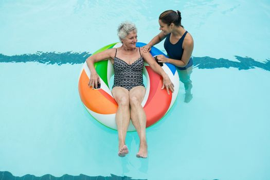Trainer assisting senior woman on inflatable ring in swimming pool