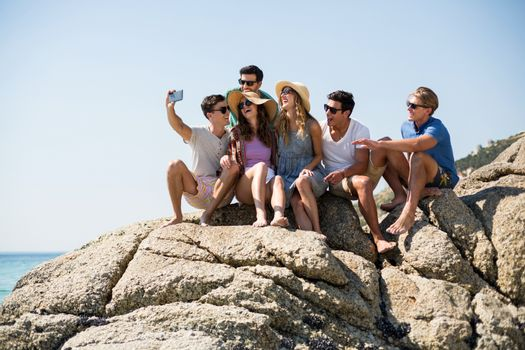 Friends taking selfie while sitting on rock formations
