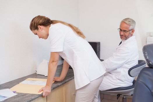 Dentist checking out his assistant