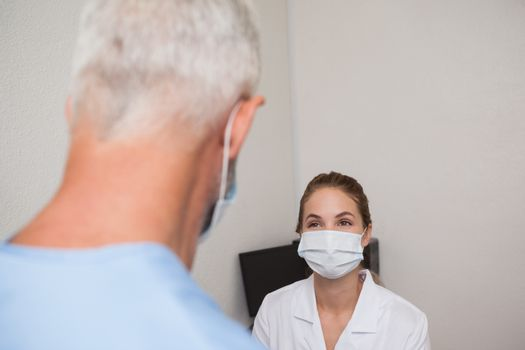 Dentist and assistant facing each other at the dental clinic
