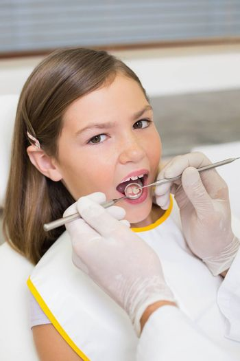 Pediatric dentist examining a little girls teeth in the dentists chair at the dental clinic