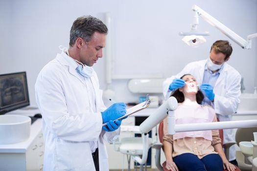 Dentist writing on clipboard in dental clinic