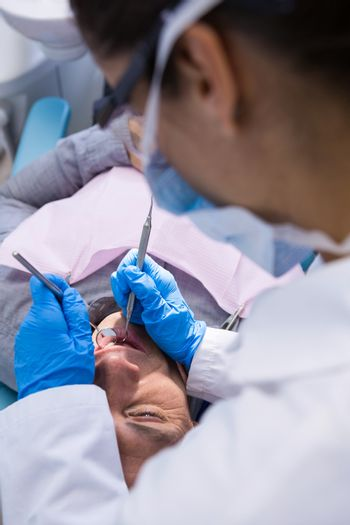High angle view of doctor giving dental treatment to man at clinic