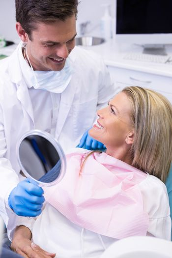 Dentist showing mirror to happy patient at dental clinic