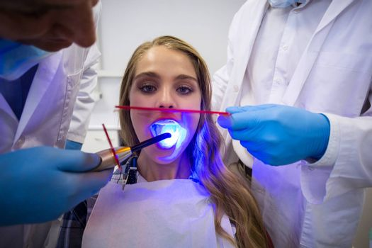 Dentists examining female patient with dental curing light in clinic
