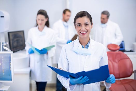 Portrait of smiling dentist holding file at dental clinic