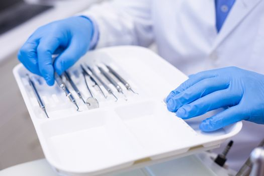 Dentist picking up dental tool at dental clinic