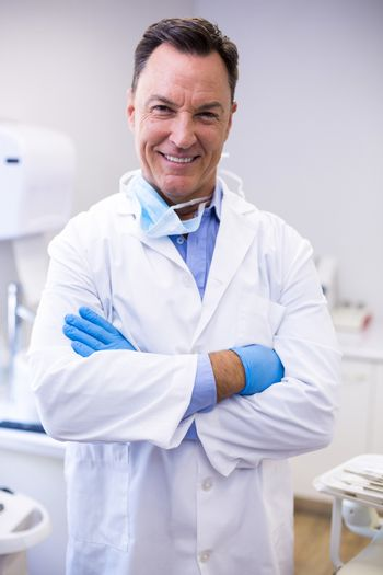 Portrait of smiling dentist standing with arms crossed at dental clinic