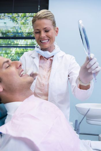Dentist showing mirrior to patient at dental clinic