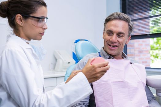 Dentist showing dental mold to man at medical clinic