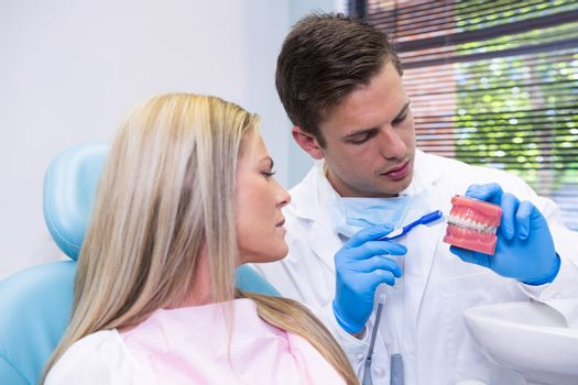 Dentist showing dental mold to woman at medical clinic