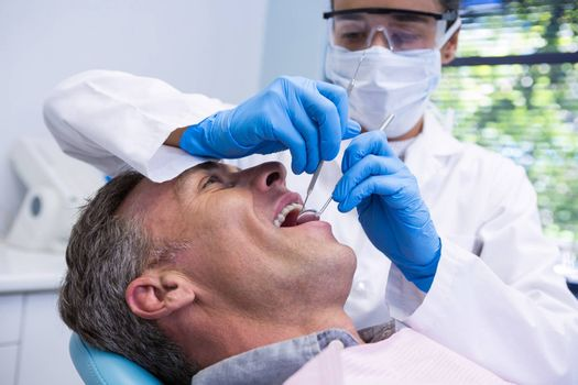 Happy man receiving dental treatment by dentist at clinic