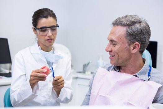 Dentist teaching man brushing teeth on dental mold at clinic