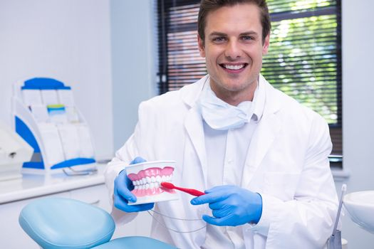 Portrait of dentist brushing dental mold while sitting at clinic