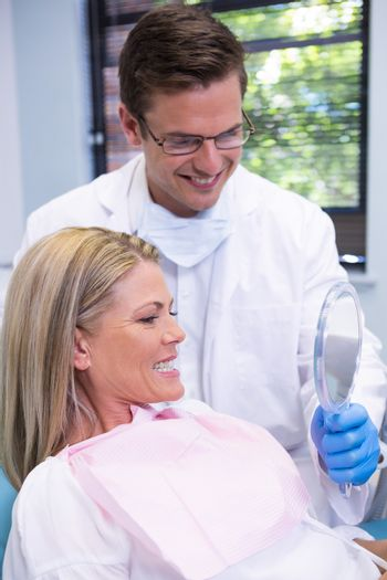 Dentist showing mirror to smiling patient at dental clinic