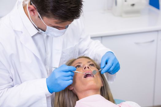 Close up of dentist examining woman at dental clinic