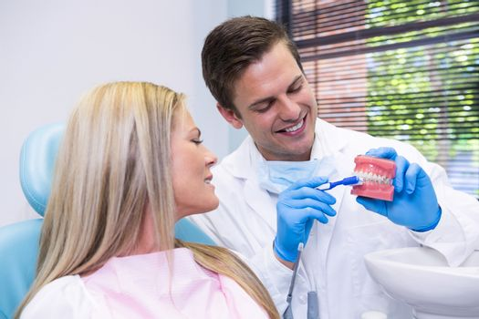 Dentist showing dental mold to patient at medical clinic