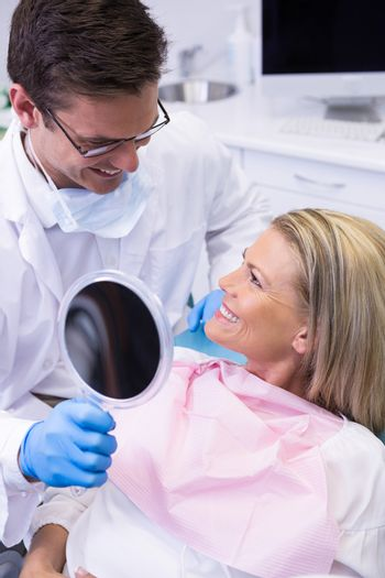 Doctor showing mirror to happy patient at dental clinic