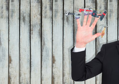 Hand with hands with tools on the fingers. Wood background
