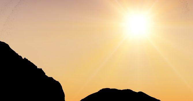 Sun shining over silhouette mountains