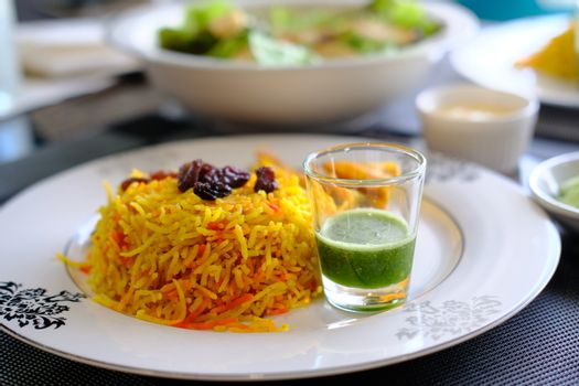 Prawn Biryani served with fried shrimp, green pepper sauce and raisins. Delicious Indian seafood traditional cuisine.