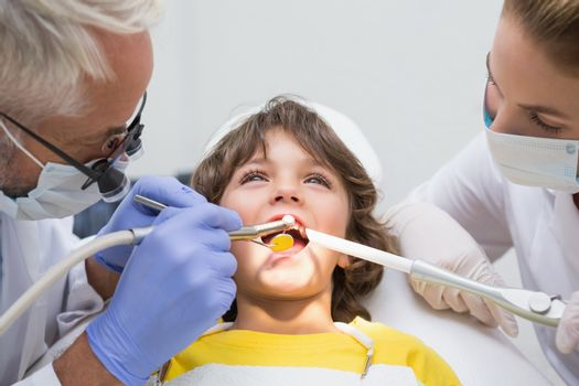 Pediatric dentist and assistant examining a little boys teeth at the dental clinic