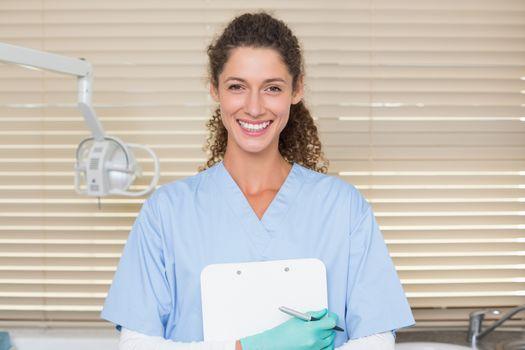 Dentist in blue scrubs holding clipboard