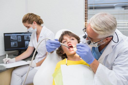 Pediatric dentist examining a little boys teeth with assistant behind at the dental clinic