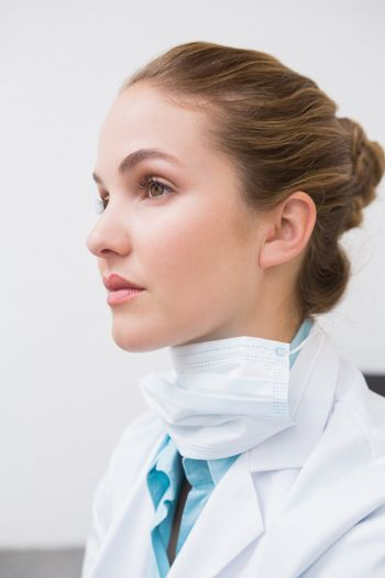 Dentist with surgical mask thinking at the dental clinic