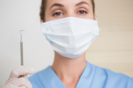 Dentist in surgical mask holding dental explorer at the dental clinic