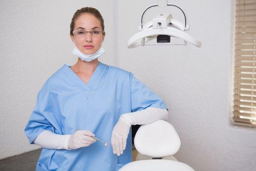 Dentist in blue scrubs looking at camera