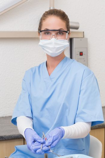 Dentist in blue scrubs holding dental tools at the dental clinic