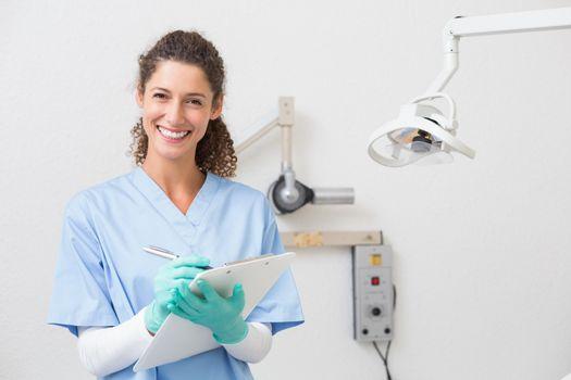 Dentist in blue scrubs writing on clipboard