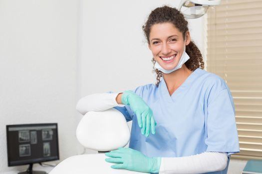 Dentist in blue scrubs smiling at camera