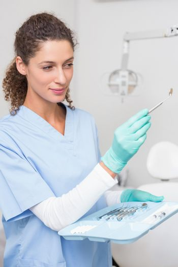Dentist in blue scrubs holding tray of tools at the dental clinic